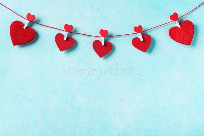 Предпосылка дня Валентайн Гирлянда красных сердец на зажимках для белья на стене бирюзы стоковые фотографии rf