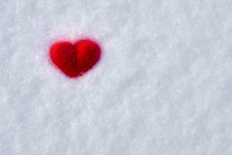 Предпосылка дня Валентайн с сердцем красных шерстей пушистым лежа на белом снеге стоковые фото