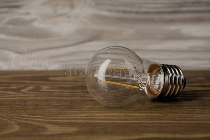 Предпосылка древесины электрической лампочки электричества лампы силы СИД стоковые фото