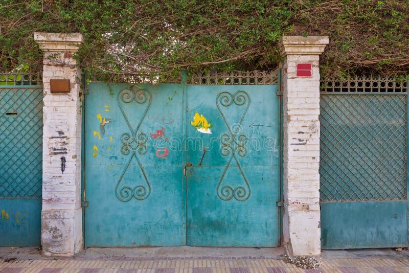 Предпосылка зеленых старых выдержанных ворот grunge античных чугунных с орнаментами цветочного узора и 2 белыми столбцами кирпиче стоковое фото rf