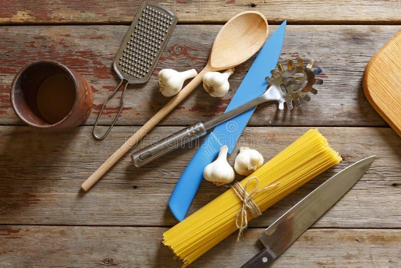 Предпосылка кухни Сдирать комплект столового прибора положения, сырцовое спагетти, овощи, травы, специи, деревянная предпосылка к стоковые изображения