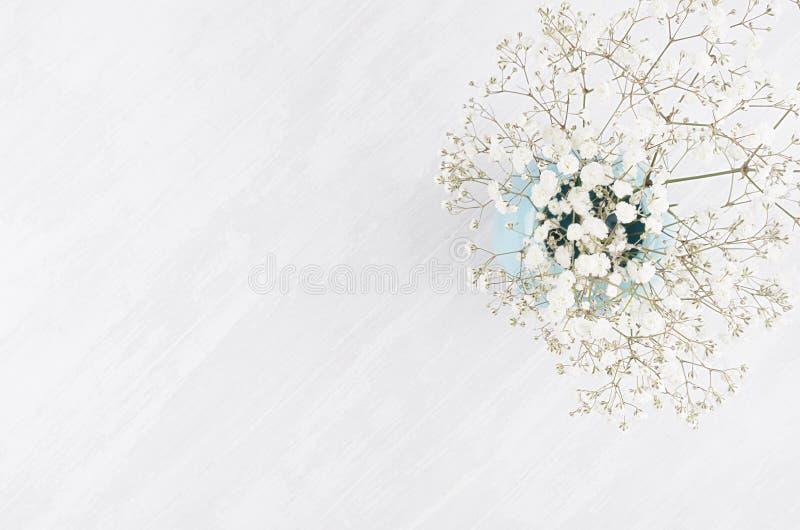 Предпосылка лета свежая с воздушными цветками в голубой вазе на белом взгляд сверху деревянной доски с космосом экземпляра стоковые изображения rf