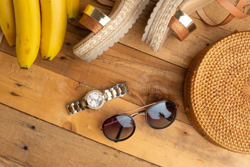 Предпосылка лета с плетеной модной сумкой, и ботинки лета женщин, бананы и стекла солнца, дозоры Мода лета, стоковые фотографии rf