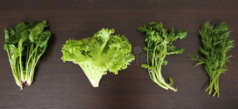 Предпосылка натуральных продуктов Комплект витамина весны различных зеленых густолиственных овощей на деревенском деревянном стол стоковое фото rf