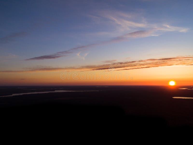 Предпосылка неба захода солнца вида с воздуха Драматическое небо захода солнца золота с облаками неба вечера над озерами Оглушать стоковая фотография