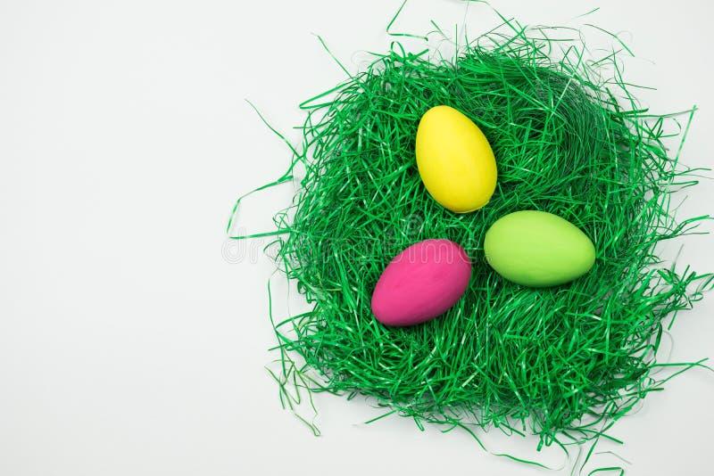 Предпосылка пасхальных яя с яйцом пинка, желтых и зеленых в зеленом гнезде на белой предпосылке стоковые фотографии rf