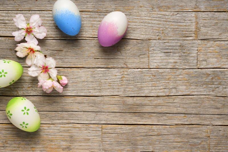 Предпосылка пасхи, пасхальные яйца и цветение миндалины на старом деревянном столе стоковое фото rf