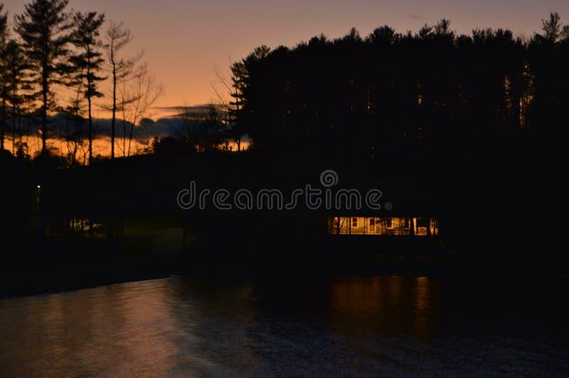 Предпосылка пейзажа сценарного ландшафта вечера захода солнца силуэта дома вида на озеро мирная стоковая фотография