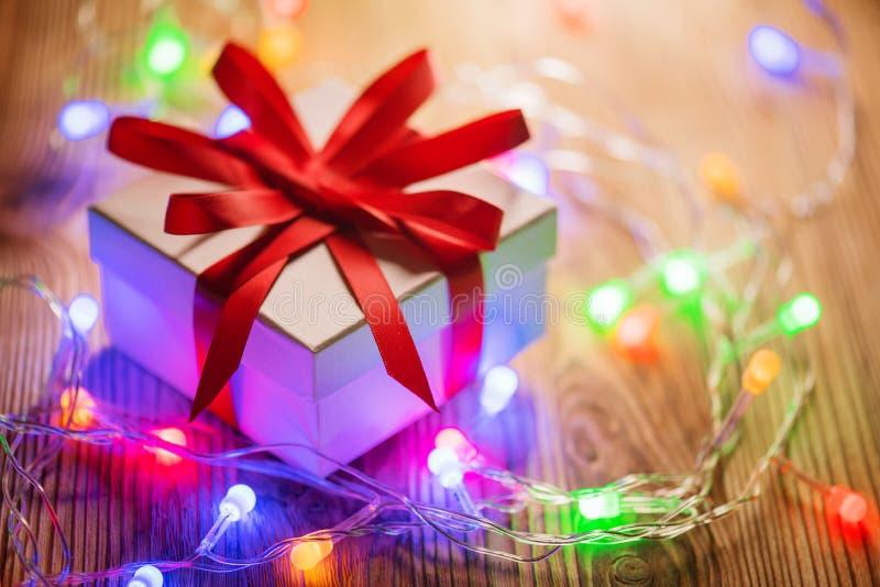 Предпосылка праздника рождества В оболочке подарочная коробка с красной лентой шелка и красочная гирлянда светов над деревянной п стоковая фотография rf