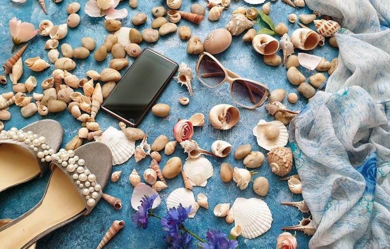 Предпосылка природы пляжа жемчуга сандалий телефона sunglass праздника моря лета аксессуаров женщин Seashell белая стоковое фото