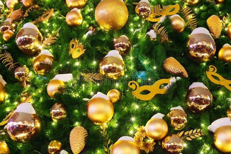 Предпосылка рождества или Нового Года праздничная, шарики украшений xmas золотые, маски, светя света гирлянды на зеленых ветвях с стоковая фотография rf
