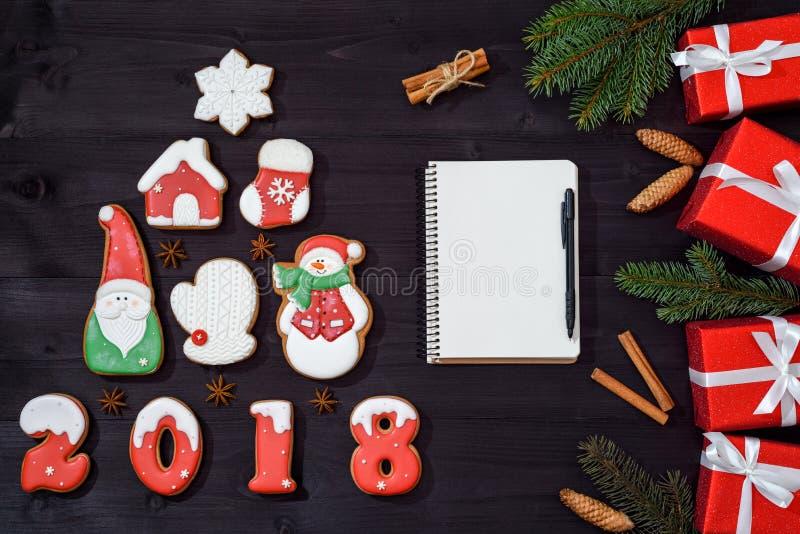 Предпосылка рождества при ель сделанная от печений пряника, пустой белой тетради с ручкой, ветвей ели и красного подарка стоковая фотография
