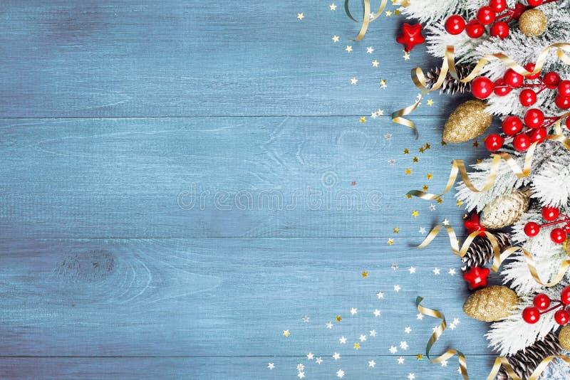Предпосылка рождества со снежными украшениями ели и праздника на голубом взгляде сверху деревянного стола текст космоса приветств стоковые изображения