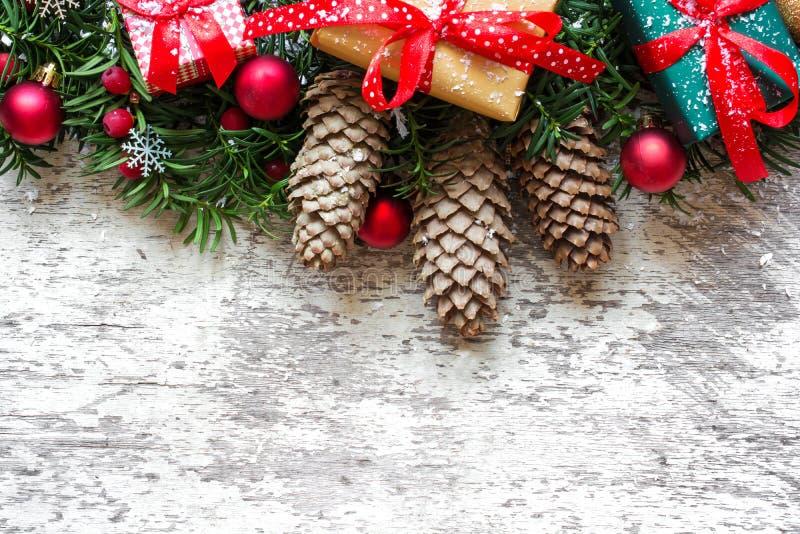 Предпосылка рождества с ветвями, украшениями и подарочными коробками ели на белой деревянной доске стоковые изображения