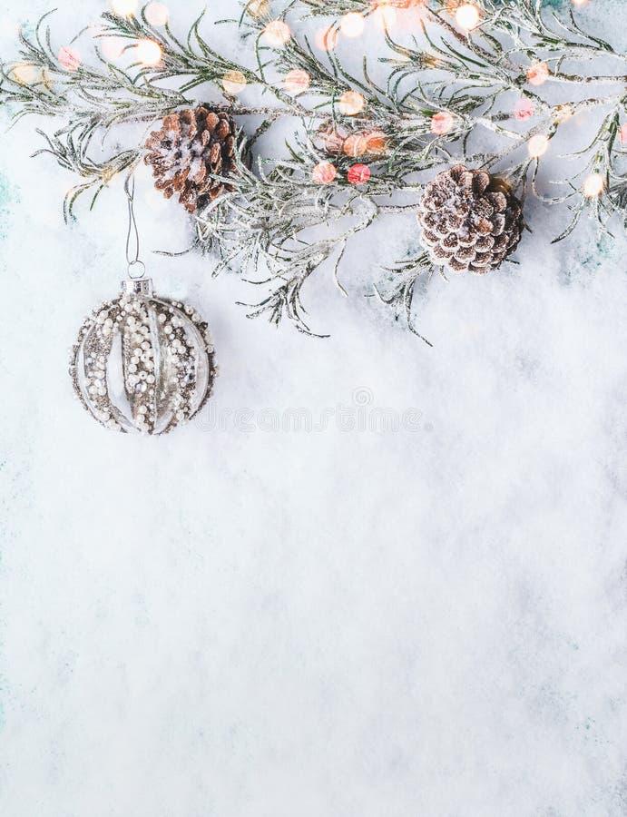 Предпосылка рождества с винтажной безделушкой, замороженными ветвями и конусами на снеге с bokeh стоковое изображение