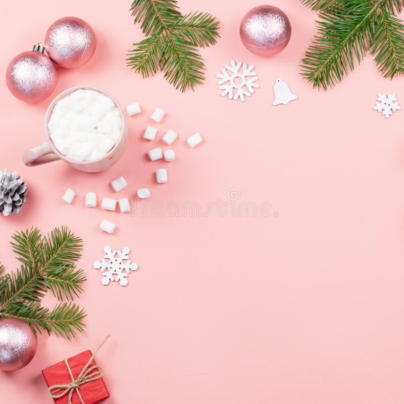 Предпосылка рождества с елью разветвляет, света, красные giftboxes, розовые украшения, горячее питье с зефирами на пинке стоковое изображение