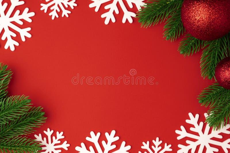 Предпосылка рождества с красными ветвями шарика и ели, снежинкой на красной бумажной предпосылке Украшение зимы стоковая фотография