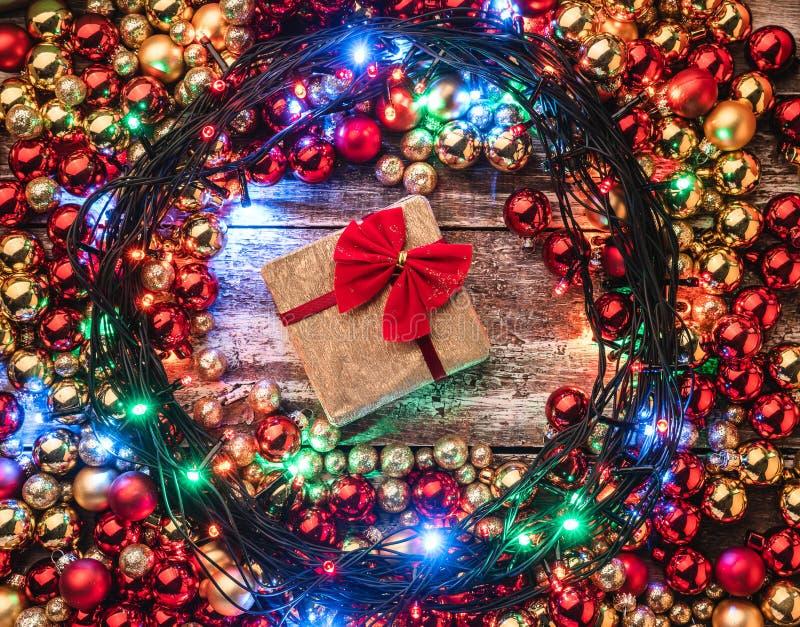 Предпосылка рождества с красным цветом и безделушками золота, освещенными вверх вокруг центра, подарок стоковые фото