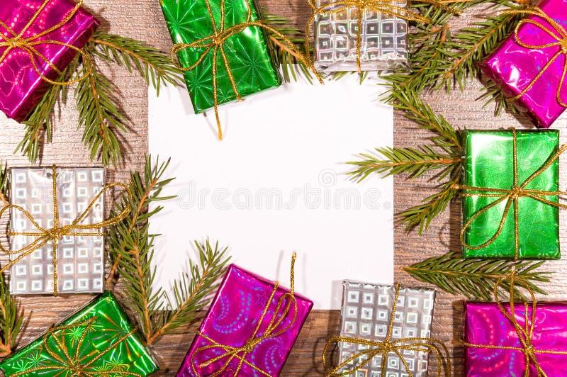 Предпосылка рождества с подарочными коробками, ветвями ели и пустым листом бумаги на деревянной доске стоковая фотография