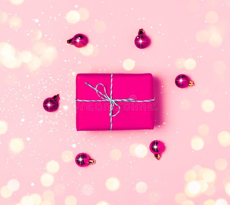Предпосылка рождества с пурпурными шариками и присутствующей подарочной коробкой и украшение на розовой предпосылке стоковые изображения