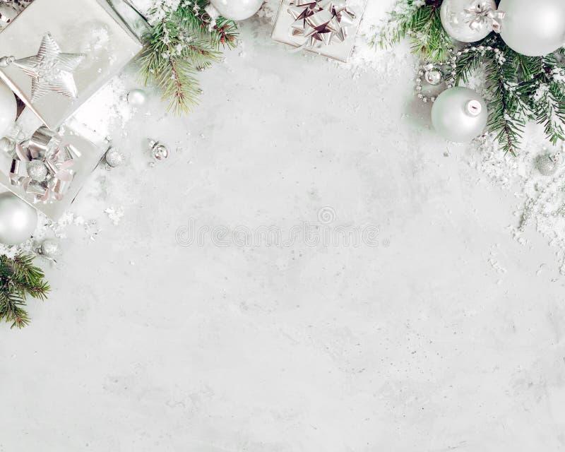 Предпосылка рождества с украшениями xmas Серебряные подарочная коробка подарка на рождество, ветвь ели и орнаменты безделушек на  стоковое изображение rf