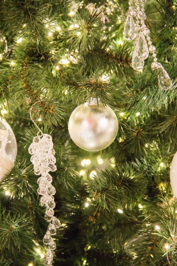 Предпосылка рождественской елки и оформление рождества Серебряный сияющий шарик и кристаллические украшения на зеленой ели стоковые фото