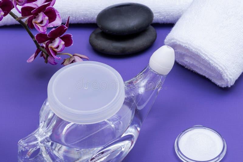 Предпосылка спа пурпурная с баком Neti, кучей соляного, свернутой вверх по белым полотенцам, штабелированным камням базальта и цв стоковая фотография