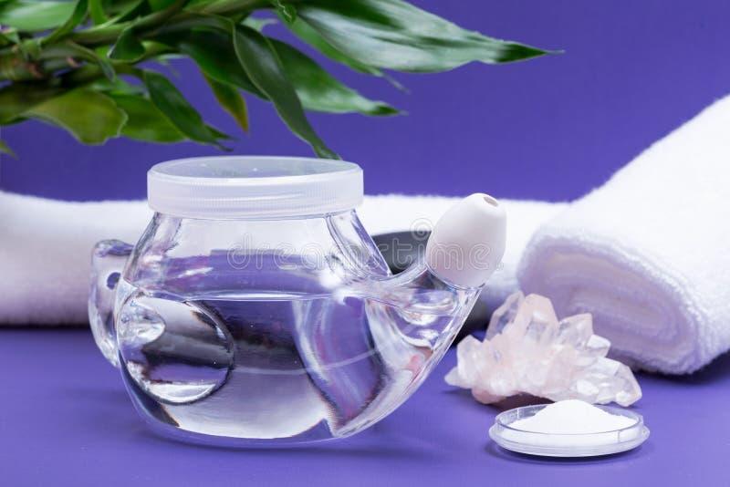 Предпосылка спа пурпурная с баком Neti, кучей соляного, свернутой вверх по белым полотенцам, штабелированным камням базальта и ба стоковое изображение rf