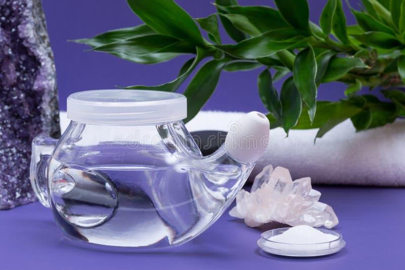 Предпосылка спа пурпурная с баком Neti, кучей соляного, свернутой вверх по белым полотенцам, штабелированным камням базальта и ба стоковые фото