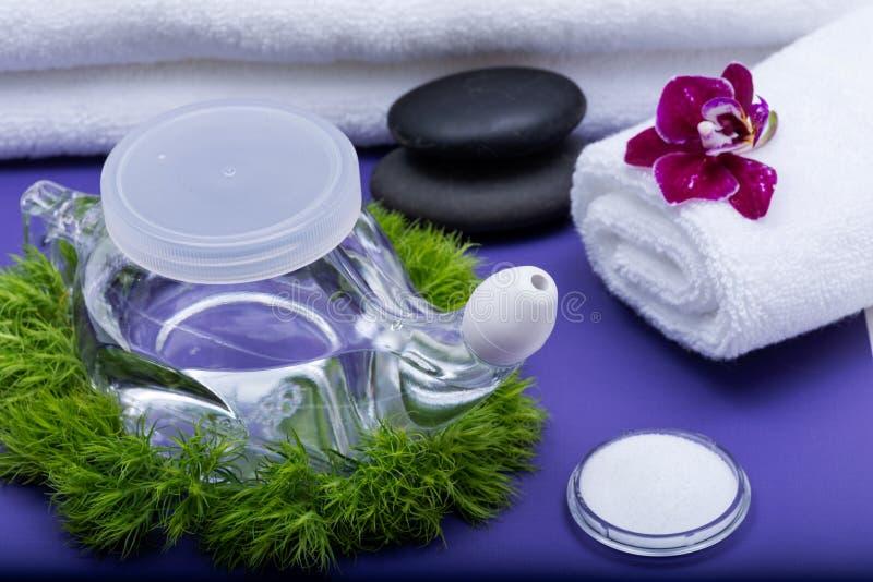 Предпосылка спа пурпурная с баком Neti, кучей соляного, свернутой вверх по белым полотенцам, штабелированным камням базальта и цв стоковые изображения rf