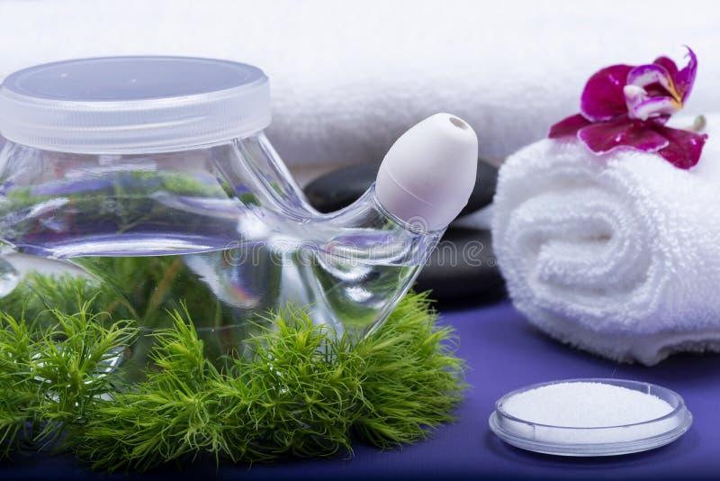 Предпосылка спа пурпурная с баком Neti, кучей соляного, свернутой вверх по белым полотенцам, штабелированным камням базальта и цв стоковое фото