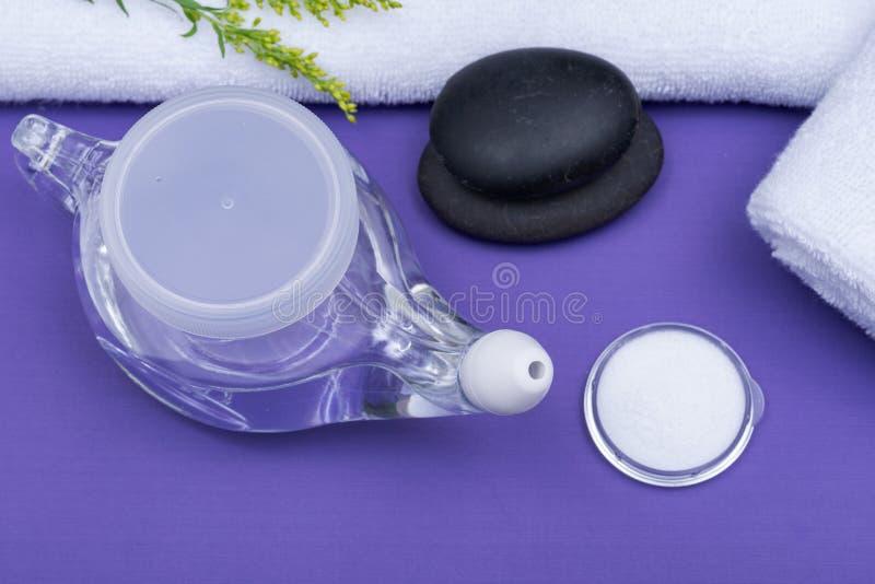 Предпосылка спа пурпурная с баком Neti, кучей соляного, свернутый вверх по белым полотенцам и штабелированным камням базальта Мыт стоковое фото rf