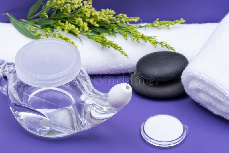 Предпосылка спа пурпурная с баком Neti, кучей соляного, свернутый вверх по белым полотенцам и штабелированным камням базальта Мыт стоковые изображения