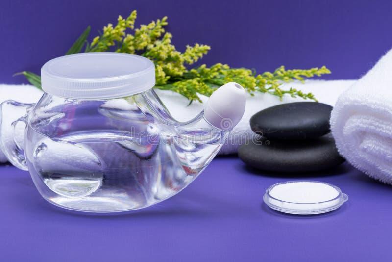 Предпосылка спа пурпурная с баком Neti, кучей соляного, свернутый вверх по белым полотенцам и штабелированным камням базальта Мыт стоковое изображение rf