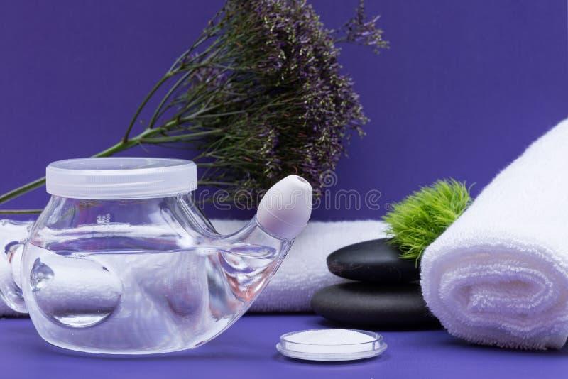 Предпосылка спа пурпурная с баком Neti, кучей соляного, свернутый вверх по белым полотенцам и штабелированным камням базальта Мыт стоковое фото
