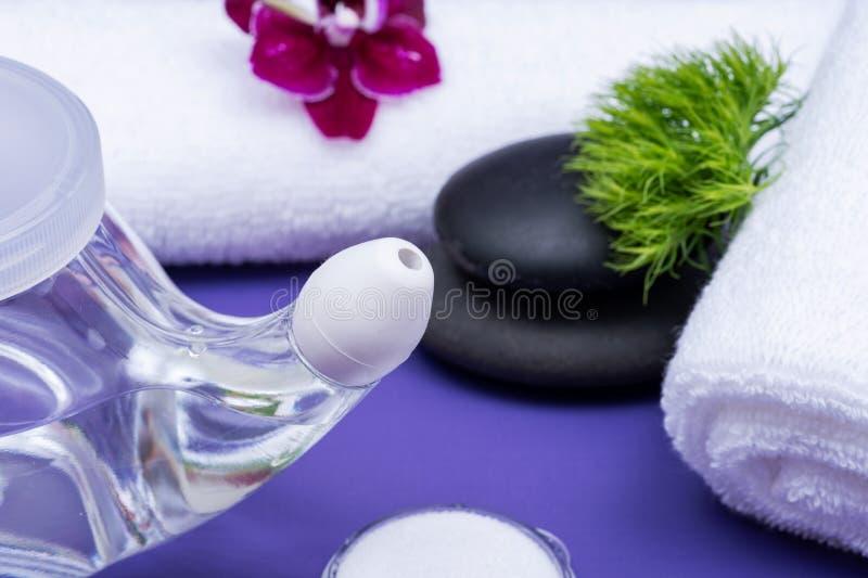 Предпосылка спа пурпурная с баком Neti, кучей соляного, свернутый вверх по белым полотенцам и штабелированным камням базальта Мыт стоковое изображение