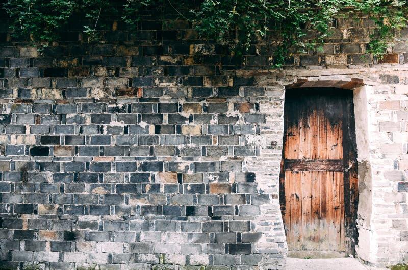 Предпосылка старых кирпичных стен штабелировала в слоях с космосом экземпляра и деревянной дверью или может использовать обои стоковые изображения rf