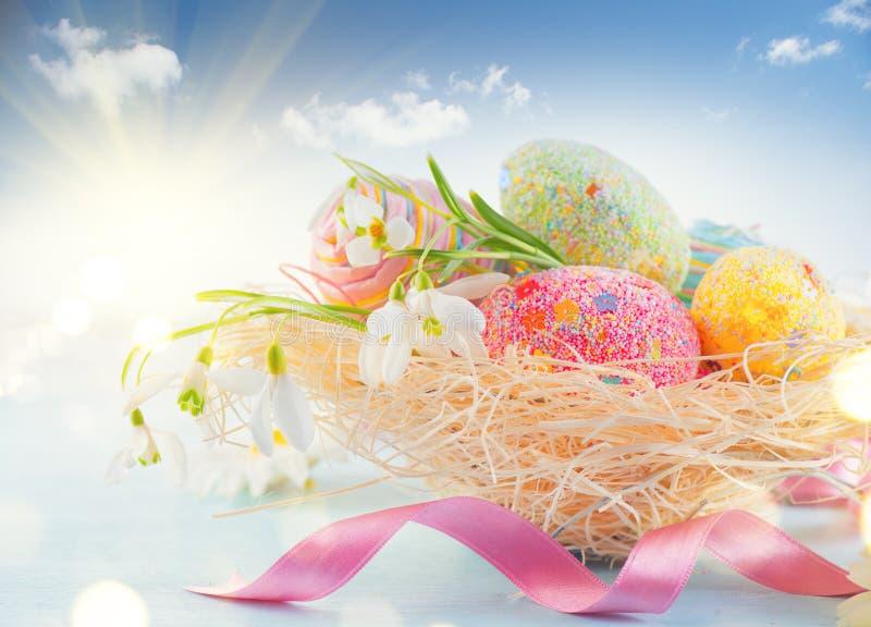 Предпосылка сцены праздника пасхи Традиционные красочные яичка и цветки весны в гнезде над голубым небом стоковые изображения rf