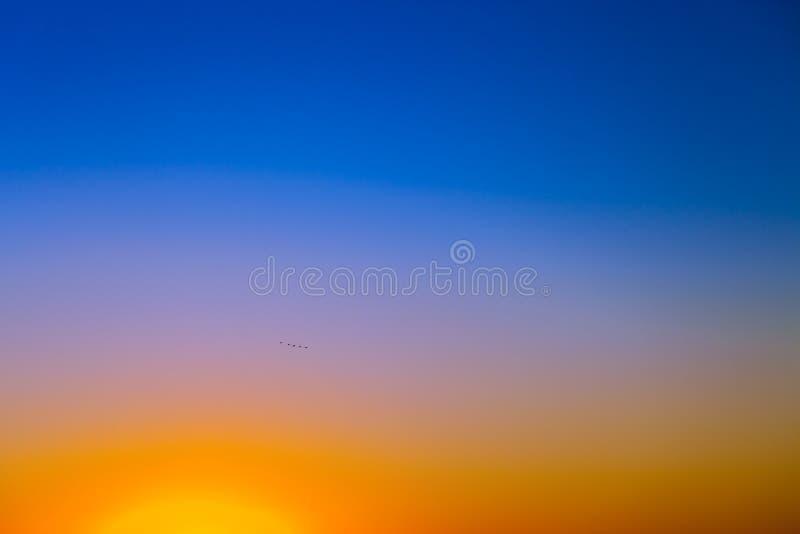 Предпосылка с небом захода солнца градиента в тонах желтой, апельсина и сини стоковое изображение