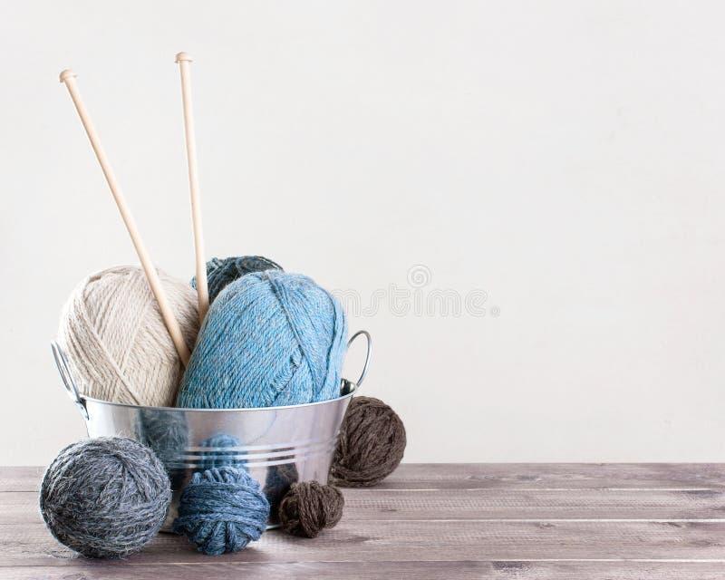 Предпосылка с шерстями и вязать иглами на деревянном столе стоковая фотография rf