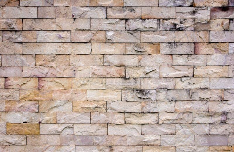 Предпосылка текстуры кирпичной стены песчаника Деталь текстуры каменной стены песка Красочная текстура каменной стены песка стоковая фотография