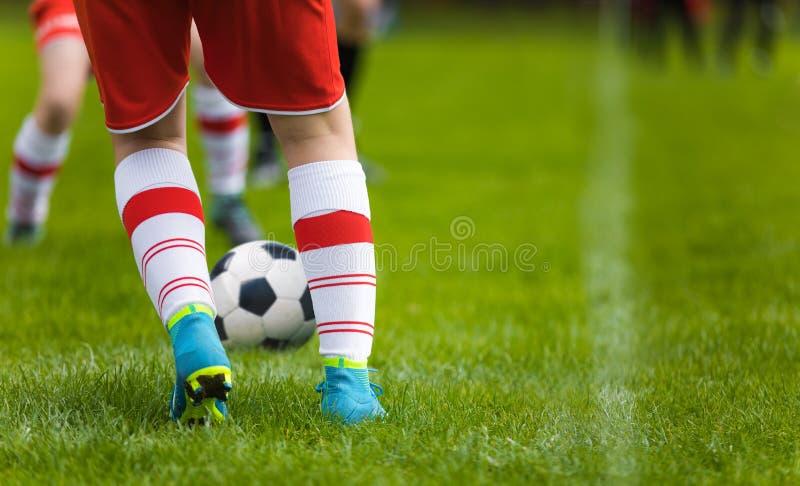 Предпосылка футбола детали Закройте вверх по ногам и ногам футболиста в белых носках и голубых зажимах играя игру на зеленой трав стоковое фото