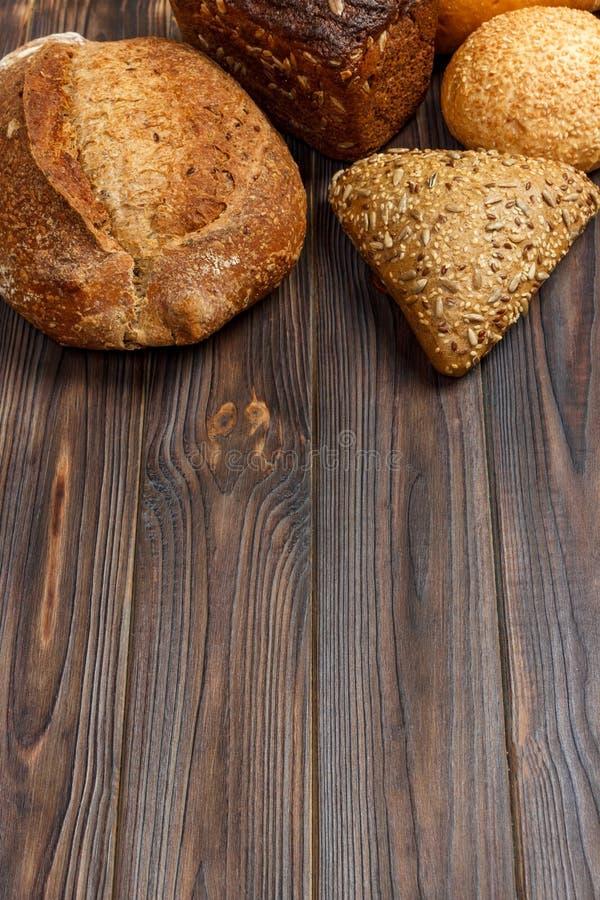 Предпосылка хлебопекарни, ассортимент хлеба на черном деревянном фоне Взгляд сверху с космосом экземпляра стоковые изображения rf