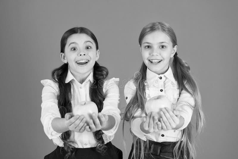 Предпосылка школьной формы детей девушек оранжевая Школьницы едят яблоки Школьный обед Питание витамина во время учебного дня стоковое изображение