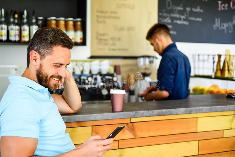 Предпосылка barista кафа сообщения человека мобильная читая Кофе напитка пока ждущ проверите сообщение Заказ смартфона человека стоковое изображение