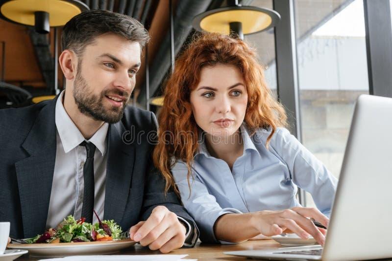 Предприниматели имея бизнес-ланч на деятельности еды ресторана сидя на усмехаться ноутбука стоковые изображения