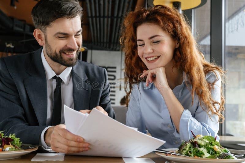 Предприниматели имея бизнес-ланч на еде ресторана сидя обсуждающ контракт жизнерадостный стоковое изображение rf