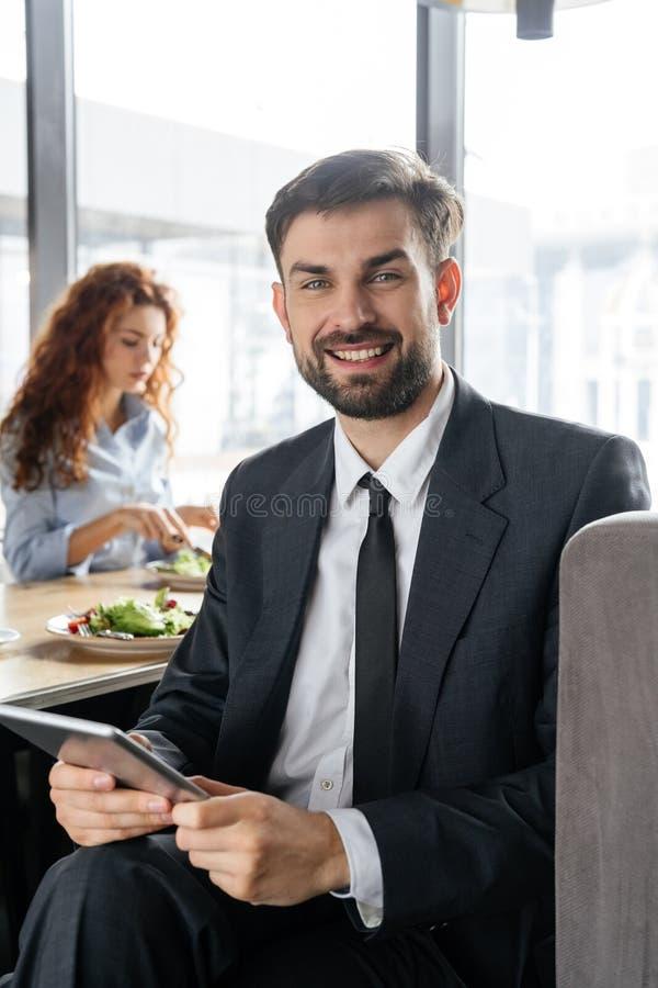 Предприниматели имея бизнес-ланч на конце-вверх человека ресторана сидя держа цифровой планшет смотря усмехаться камеры стоковая фотография