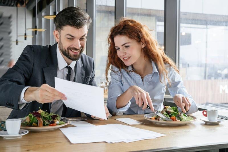 Предприниматели имея бизнес-ланч на условиях документа женщины показа человека еды ресторана сидя счастливых стоковая фотография rf