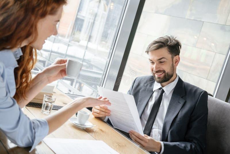 Предприниматели имея перерыв на чашку кофе на эспрессо ресторана сидя выпивая обсуждая контракт жизнерадостный стоковые изображения